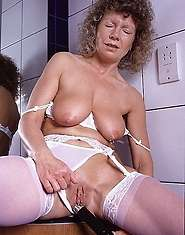 Granny oils up and spreads for her dildo