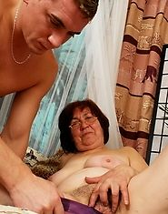 Dirty granny in glasses fools around with a younger man
