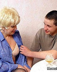 A chubby mature blond gives head to two youngsters on the table